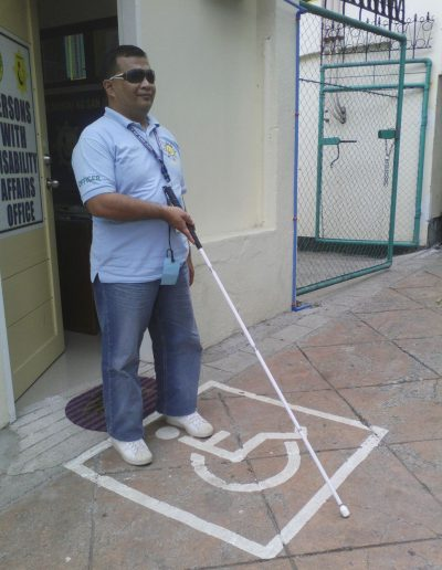 Blind man in sun glasses, light blue shirt, blue jeans and white shows using a white straight cane.